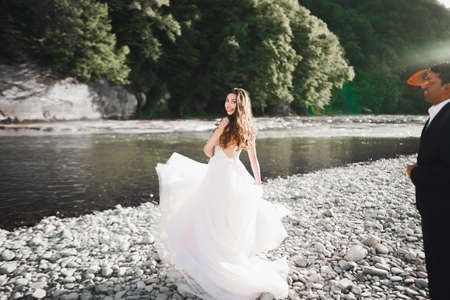 Elegant stylish happy blonde bride and gorgeous groom on the background of a beautiful river in the mountains