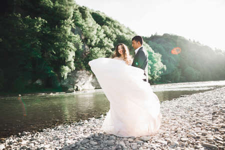 Sunshine portrait of happy bride and groom outdoor in nature location