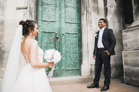 A loving wedding couple are walking back along the streets of the city of Lviv