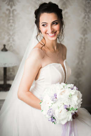 Gorgeous bride in robe posing and preparing for the wedding ceremony face in a room Zdjęcie Seryjne