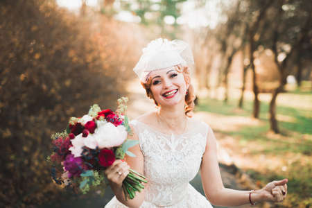 Beautiful bride in elegant white dress holding bouquet posing in park Stockfoto