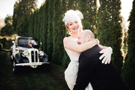 Happy newlywed couple, man and wife kissing near stylish retro car