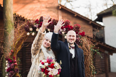 Perfect wedding couple holding luxury bouquet of flowers