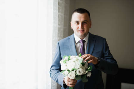 Beautiful man, groom holding big and beautiful wedding bouquet with flowers Stock fotó
