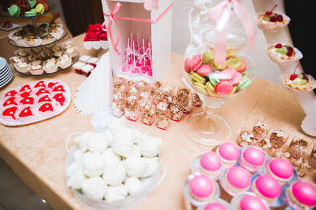 Delicious and tasty dessert table with cupcakes and shots at reception closeup
