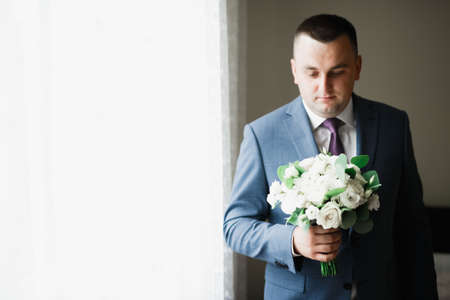 Beautiful man, groom holding big and beautiful wedding bouquet with flowers