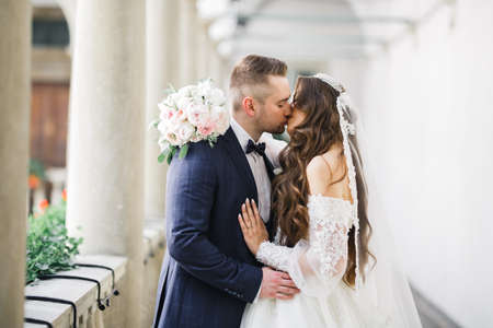 Beautiful bride and groom embracing and kissing on their wedding day