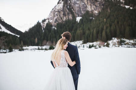 Beautiful young couple in winter mountains. Winter walk of lovers. Man hugging woman