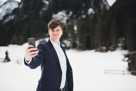 Groom on the nature making a selfie. Man in suit