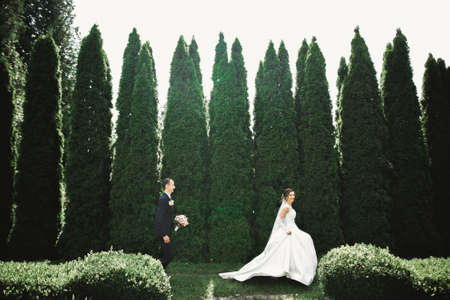 Stylish couple of happy newlyweds.Bride running from groom in the park on their wedding day with bouquet Standard-Bild