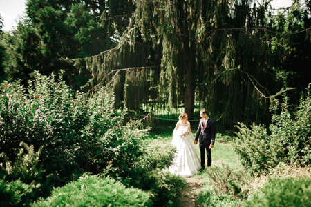 Stylish couple of happy newlyweds walking in the park on their wedding day with bouquet Standard-Bild