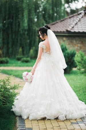 Beautiful bride in elegant white dress holding bouquet posing in park Standard-Bild