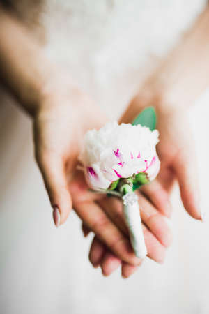 Beautiful luxury bride in elegant white dress holds bouquet of flowers in the hands