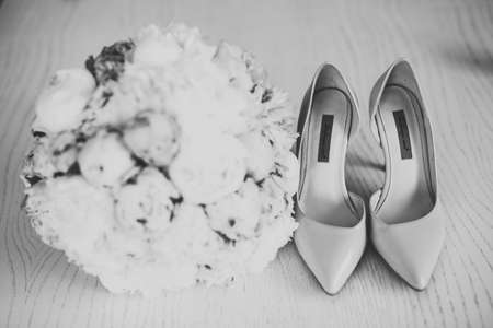 Pair of elegant and stylish bridal shoes with a bouquet with roses and other flowers.
