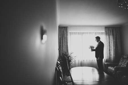 Grooms morning preparation. Handsome man getting dressed and preparing for the wedding Standard-Bild
