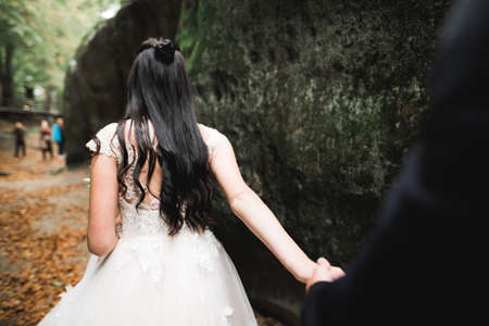 Woman with beautiful hair discovering beautiful places holding boyfriends hand. Follow me