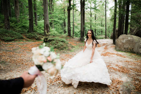 Stylish couple of happy newlyweds. Bride running from groom in the park on their wedding day with bouquet