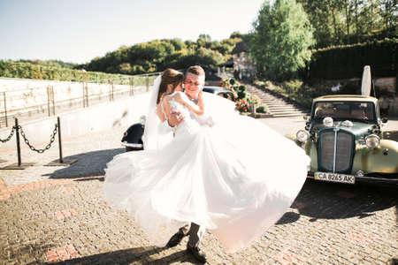 Wedding bride and groom, elegant couple staying near retro wedding car Stock Photo
