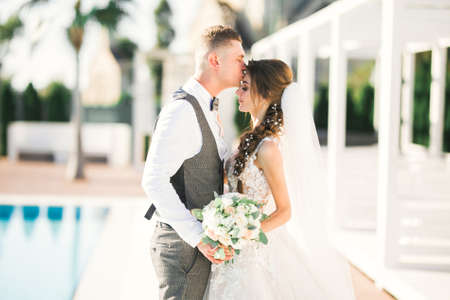 Wedding couple is hugging each other. Beautiful model girl in white dress. Man in suit Stock Photo