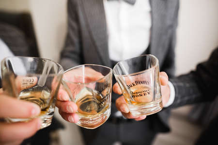 Business meeting. Men hold glasses of whiskey. Mens Party. Hand with a drink of alcohol Stock Photo