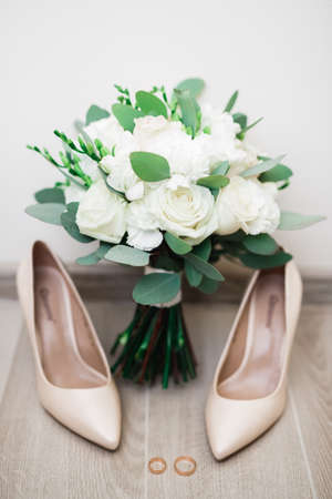 Pair of elegant and stylish bridal shoes with wedding rings and a bouquet of roses and other flowers