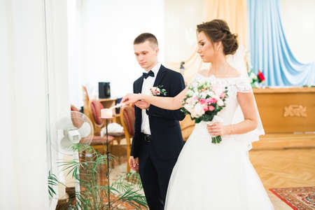 Bride and groom holding candles in church