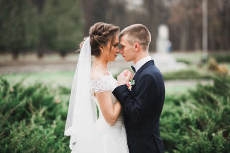 Gorgeous happy couple standing close to each other and looking in eyes