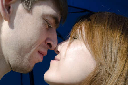 A young couple in love under the blue umbrella - face to face Stock Photo - 14027862
