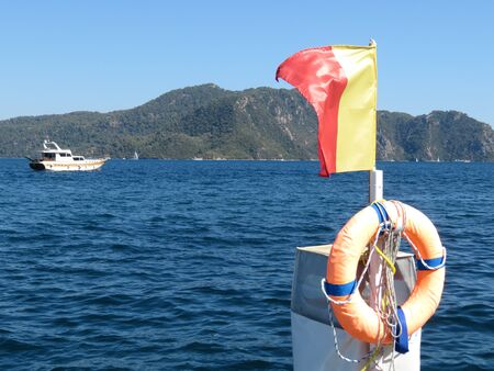 Red-yellow flag and life preserver on the beach in the Aegean sea
