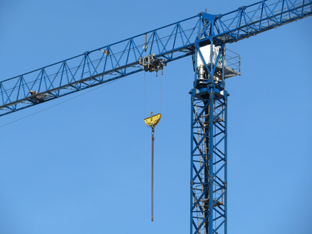 Construction crane on background of blue sky