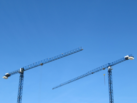 Construction cranes on the background of clear blue sky. Tower cranes