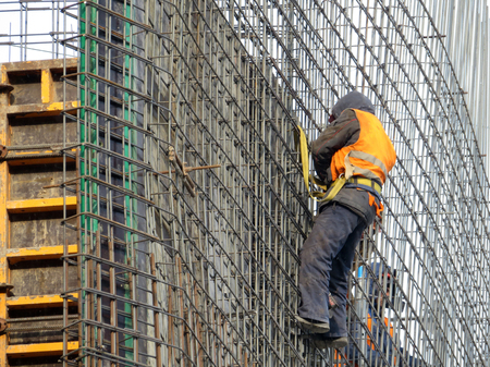 Steeplejack on the scaffolding. Builder Worker at the construction site