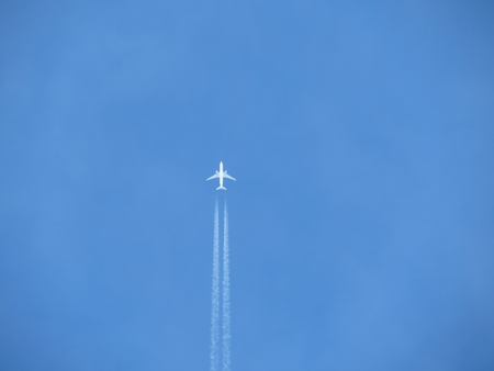 White trace of a plane across the blue sky. Jet airplane is flying high