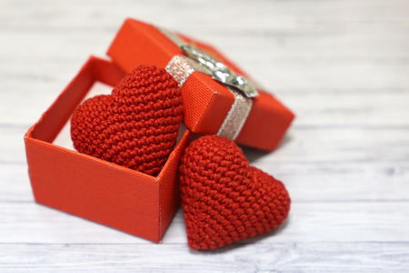 Valentine gift box with red knitted hearts on light wooden table. Love concept