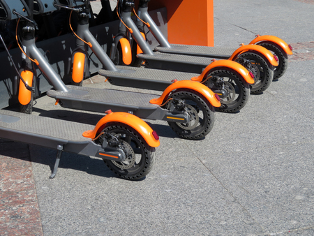 Electric scooters in row on the parking lot. City bike rental system, public kick scooters on the street