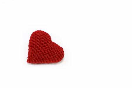 Red knitted heart isolated on white background. Symbol of love, blood donation, valentines day
