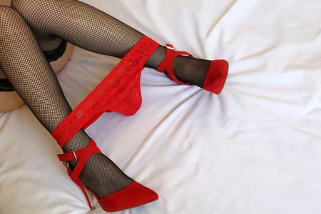 Schlanke weibliche Beine mit roten Spitzenhöschen unten. Absätze von Frauen Standard-Bild