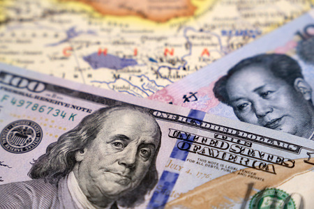 Chinese Yuan and US dollars on the map of China. Trade war between US and China, economic sanctions Banco de Imagens