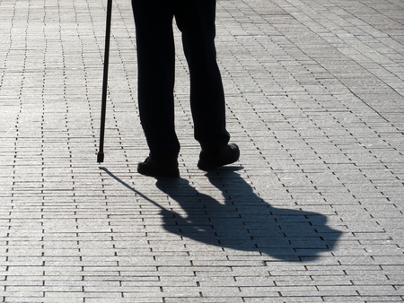Silhouette of limping man walking with cane long shadow on pavement. Concept for disability, old age, blind person, dramatic life Zdjęcie Seryjne