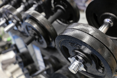 Dumbbells on rack in the gym. Concept of fitness center, sports equipment, bodybuilding, weightlifting Banco de Imagens