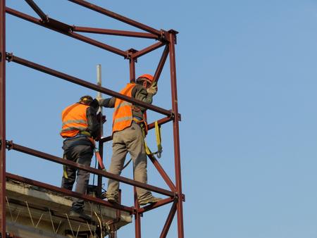 Construction workers working on scaffolding. Welders blue sky