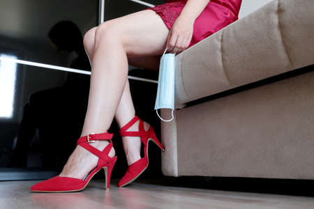 Woman with removed medical mask sitting on a sofa, sex at quarantine during the coronavirus pandemic. Sexy girl wearing red shoes on high heels Banque d'images