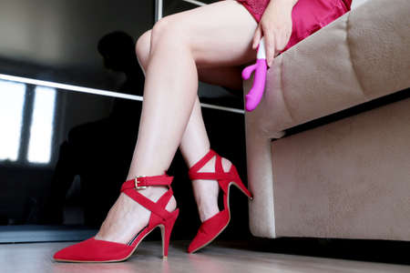 Sexy woman in red nightie and shoes on high heels sitting on the sofa with dildo in hand. Sex toy, adult games concept