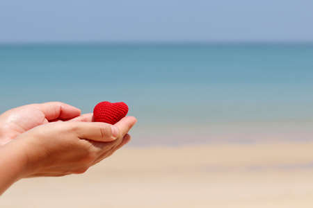 Sea vacation and love on a sandy beach, red knitted heart in a female hands against the blue water. Concept of romantic travel and honeymoon