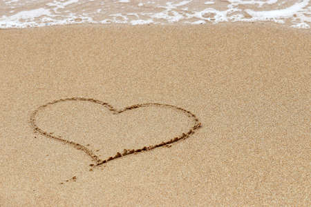 Heart drawing on a sand of beach on sea wave background. Concept of fleeting love, holiday romance, romantic travel