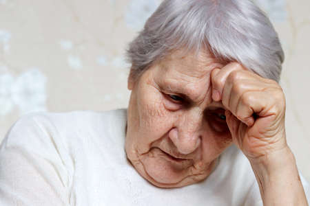Elderly woman thought about something. Sad female with gray hair and wrinkled skin, concept of headache, memories, loneliness and old age Standard-Bild