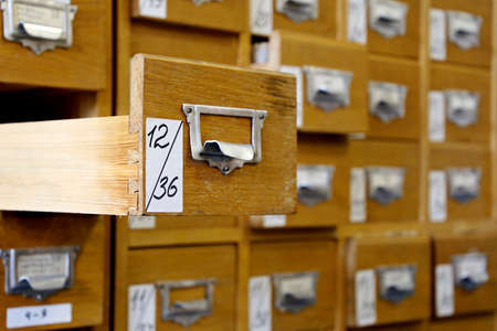 Library catalog cards in old wooden box. File archive, opened drawer with paper documents, database concept