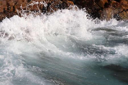 Waves break on rocks on the seashore. Clean foamy water on a stones, sea storm