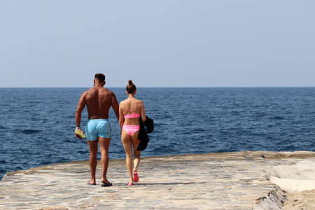 Couple walking on a stone beach on sea background. Muscular man in blue trunks and girl in pink bikini together, romantic holiday and beach vacation