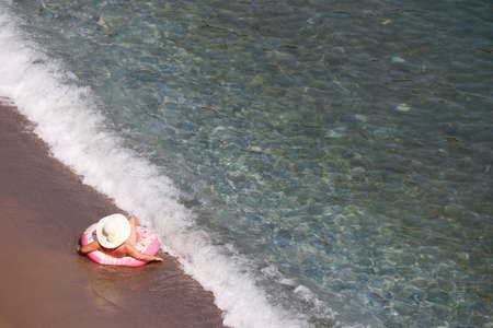 Woman in sun hat laying on inflatable donut ring on a sand in sea waves